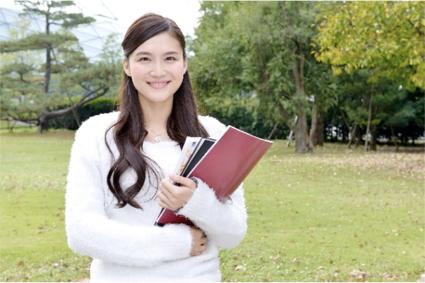 ノートと教科書をもって微笑む女学生の写真